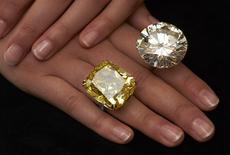 A model poses with a vivid yellow 100.09 carats diamond (L) and a 103.46 carats diamond ring during an auction preview at Sotheby's in Geneva May 7, 2014.  REUTERS/Denis Balibouse