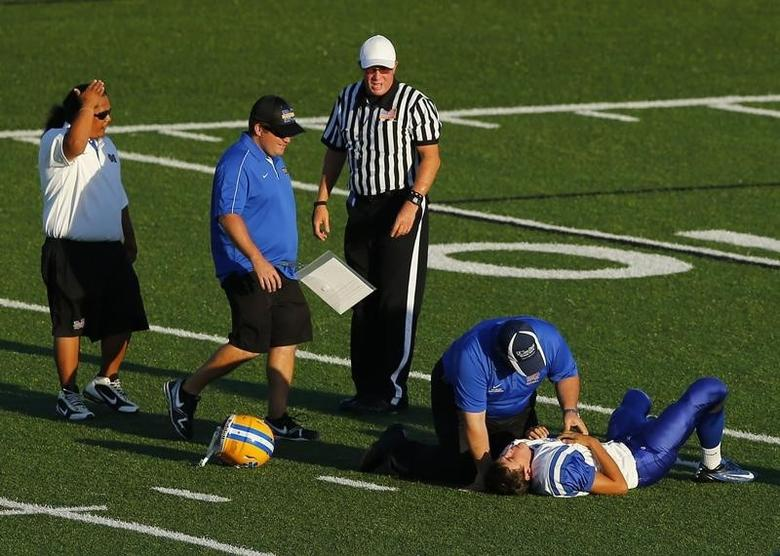A Mira Mesa junior varsity high school football player is attended to by training staff after being hit by an Oceanside Pirates player during their game in Oceanside, California September 14, 2012.REUTERS/Mike Blake