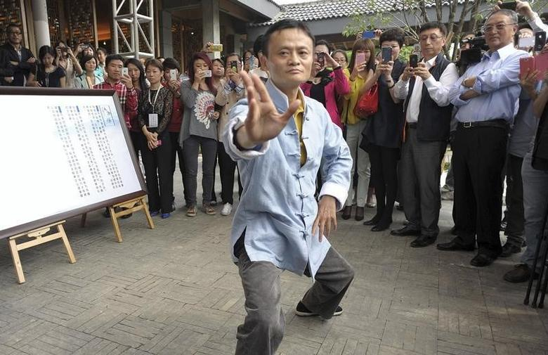 Jack Ma (C), chairman of China's largest e-commerce firm Alibaba Group, performs Tai Chi as guests and visitors take pictures and videos, at a opening ceremony of a Tai Chi school in Hangzhou, Zhejiang province May 10, 2013. REUTERS/China Daily/Files