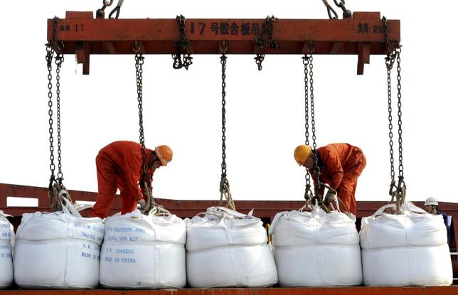 Workers load bags of chemicals onto a ship for export at a port in Lianyungang, Jiangsu province, May 8, 2014. REUTERS/China Daily