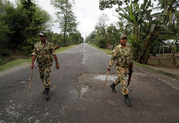Security personnel patrol a deserted road during a curfew in Baksa district in Assam May 4, 2014. REUTERS/Utpal Baruah