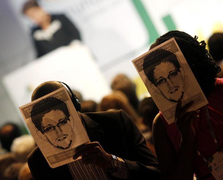 People hold masks depicting Edward Snowden during the NETmundial: Global Multistakeholder Meeting on the Future of Internet Governance in Sao Paulo April 23, 2014 file report.   REUTERS/Nacho Doce