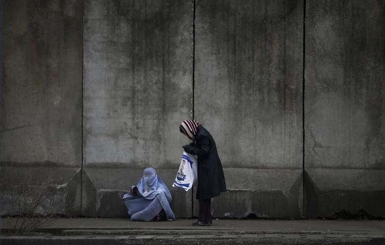 A woman (R) stops to give money to a beggar wearing a burqa outside a police station in Kabul April 2, 2014.    REUTERS/Tim Wimborne