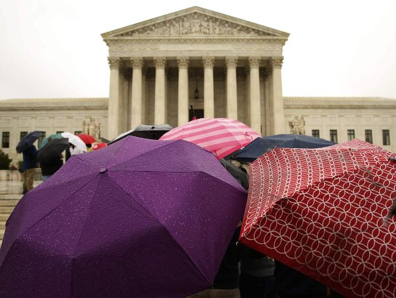 People huddle under their umbrellas while waiting for admittance outside of the U.S. Supreme Court in Washington April 29, 2014. REUTERS/Gary Cameron/Files
