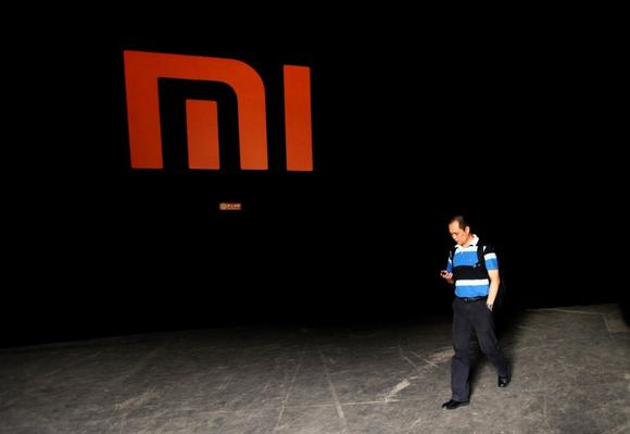 A man checks his mobile phone as he walks past a logo of Xiaomi during its Phone 2 launch ceremony in Beijing August 16, 2012. REUTERS/Jason Lee/Files