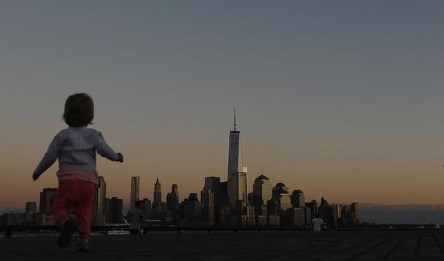 A girl plays in front of the skyline of New York's Lower Manhattan and One World Trade Center in a park along the Hudson River in Hoboken, New Jersey, September 5, 2013.  REUTERS/Gary Hershorn
