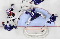 France's goalkeeper Cristobal Huet (C) defends during the men's ice hockey World Championship Group A game against Canada at Chizhovka Arena in Minsk May 9, 2014. Reuters/Vasily Fedosenko