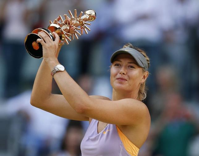 Maria Sharapova of Russia celebrates holding the Ion Tiriac trophy after winning the Madrid Open final tennis match over Simona Halep of Romania in Madrid May 11, 2014. REUTERS/Andrea Comas
