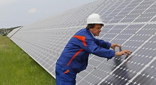 A worker inspects solar panels at Enel's power plant in Montalto di Castro, central italy, April 27, 2011. REUTERS/Max Rossi