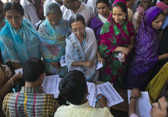 Voters get their names checked in a voter's lists at a polling station during the final phase of the general election in Varanasi in Uttar Pradesh May 12, 2014. REUTERS/Ahmad Masood