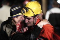 Горняк обнимает свою родственницу у шахты в городе Сома 14 мая 2014 года. Взрыв и последовавший за ним пожар на шахте в западной Турции унесли жизни как минимум 201 человека, сотни горняков по-прежнему остаются под землей, и число погибших в результате крупнейшей подобной аварии в стране за последние 20 лет может увеличиться. REUTERS/Osman Orsal
