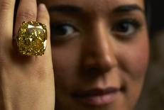 A model poses with a vivid yellow 100.09 carats diamond during an auction preview at Sotheby's in Geneva May 7, 2014. REUTERS/Denis Balibouse