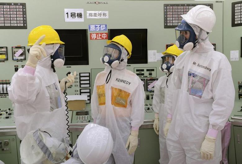 Wearing a protective suit and a mask, U.S. Ambassador to Japan Caroline Kennedy (C) and her son Jack Kennedy Schlossberg (R) listen to Naohiro Masuda (L), an executive of Japan's Tokyo Electric Power Co. (TEPCO) during her visit to the central control room for the unit one and unit two reactors of the tsunami-crippled Fukushima Daiichi nuclear plant at Okuma town in Fukushima prefecture May 14, 2014. REUTERS/Toru Yamanaka/Pool