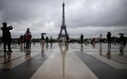 Tourists stroll on the Trocadero square, in front of the Eiffel Tower during a rainy summer day in Paris, August 7, 2013. REUTERS/Christian Hartmann