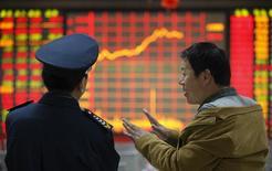 Инвестор разговаривает с охранником в брокерской конторе в Хуайбэе 8 апреля 2014 года. Азиатские фондовые рынки, кроме Японии, завершили неделю ростом за счет отдельных отраслей и локальных факторов. REUTERS/Stringer