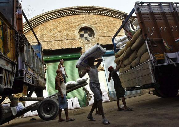 Labourers unload grocery items from supply trucks at a wholesale market in Kolkata May 15, 2014. REUTERS/Rupak De Chowdhuri