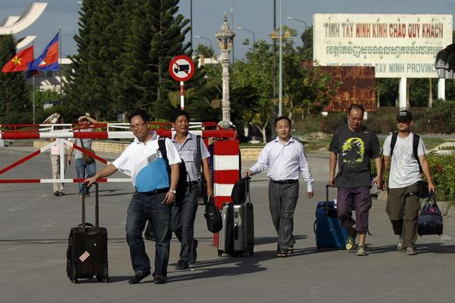 Chinese nationals cross to Cambodia from Vietnam at the Bavet international checkpoint in Svay Rieng province May 15, 2014. REUTERS/Samrang Pring