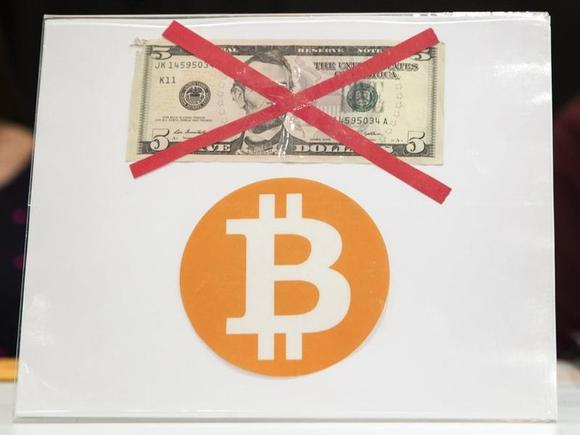 A Bitcoin logo is displayed below a $5 bill during the ''Inside Bitcoins: The Future of Virtual Currency Conference'' in New York April 8, 2014. REUTERS/Lucas Jackson/Files