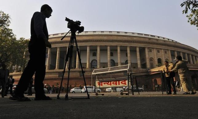 Television journalists report from the premises of Parliament in New Delhi February 13, 2014. . REUTERS/Adnan Abidi/Files
