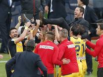 """Игроки """"Атлетико"""" качают на руках главного тренера команды Диего Симеоне после победы в чемпионате Испании в Барселоне 17 мая 2014 года. Мадридский """"Атлетико"""" в гостях сумел отыграться в матче с """"Барселоной"""", завершив субботний матч вничью 1-1 и став чемпионом Испании впервые за 18 лет. REUTERS/Gustau Nacarino"""