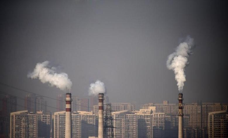 Smoking chimneys are seen in front of residential buildings in Tianjin January 17, 2013.  REUTERS/Petar Kujundzic