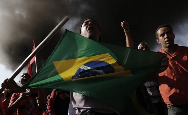Members of Brazil's Homeless Workers' Movement (MTST), who are living at the ''People's World Cup Camp'' which houses some 2,800 families of the movement in the district of Itaquera near Sao Paulo's World Cup stadium, Arena de Sao Paulo, block a road during a protest against the 2014 World Cup in Sao Paulo, May 15, 2014. REUTERS/Nacho Doce