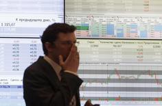 Сотрудник биржи ММВБ стоит у экрана с рыночными котировками и графиками в Москве 1 июня 2012 года. Российские фондовые индексы в начале торгов вторника продолжили повышение предыдущих сессий, и рынок ожидает в ближайшие дни подписания газового соглашения между Газпромом и Китаем во время визита президента РФ Владимира Путина в Пекин. REUTERS/Sergei Karpukhin