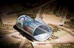 Купюры валют рубль и евро в Москве 17 февраля 2014 года. Рубль начал торги снижением к доллару и бивалютной корзине, фактор поддержки налоговых платежей немного утрачивает свой эффект, уступая место коррекции курса после укрепления с конца прошлой недели на 0,7 процента к доллару и бивалютной корзине. REUTERS/Maxim Shemetov