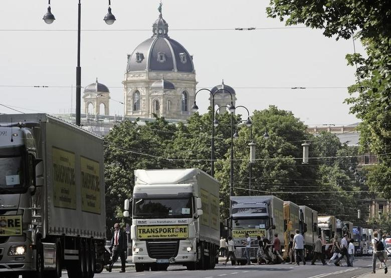 Trucks drive slowly as part of a freight carrier's demonstration demanding lower taxes and governmental aid for reduced-emission trucks on Ringstrasse street in front of the Museum of Natural History in Vienna May 25, 2009.  REUTERS/Heinz-Peter Bader