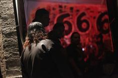 Католический священник Адольфо Уэрта ждет друзей у рок-бара в Сальтильо 23 февраля 2013 года. Российские власти велели покинуть страну польской рок-группе Behemoth, уличив в нарушении правил въезда музыкантов, чей сценический образ вызвал протесты у поборников православия. REUTERS/Daniel Becerril