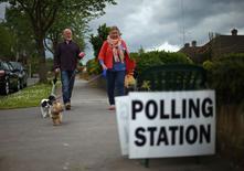 Люди идут на избирательный участок в Лондоне 22 мая 2014 года. Европейский парламентский марафон стартовал в четверг: избирательные участки открылись в Великобритании и Нидерландах, где, как ожидается, победу одержат ультраправые антиевропейские партии. REUTERS/Andrew Winning