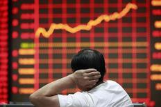 Инвестор смотрит на экран с динамикой рыночных котировок в брокерской конторе в Хуайбэе, провинция Аньхой, 9 сентября 2013 года. Азиатские фондовые рынки завершили неделю ростом за счет улучшения макроэкономической статистики и локальных факторов. REUTERS/Stringer