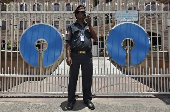 A security personnel stands guard in front of the gate of the State Bank of India (SBI) regional office in Kolkata May 23, 2014. REUTERS/Rupak de Chowdhuri