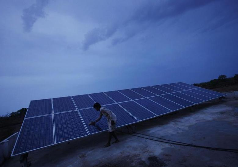 A man cleans panels installed at a solar plant at Meerwada village of Guna district in Madhya Pradesh June 18, 2012. REUTERS/Adnan Abidi/Files