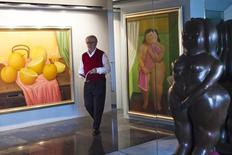 El artista figurativo colombiano Fernando Botero camina por su apartamento en Nueva York, antes de una entrevista con Reuters.  Un retrato de familia de Botero y una representación de la confusión psicológica, obra del pintor chileno Roberto Matta, estarán entre lo más destacado de las subastas de arte latinoamericano de la semana próxima en Nueva York. REUTERS/Eduardo Munoz