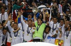 Real Madrid's captain Iker Casillas and team mates celebrate with the trophy after defeating Atletico Madrid in their Champions League final soccer match at the Luz Stadium in Lisbon, May 24, 2014.    REUTERS/Kai Pfaffenbach