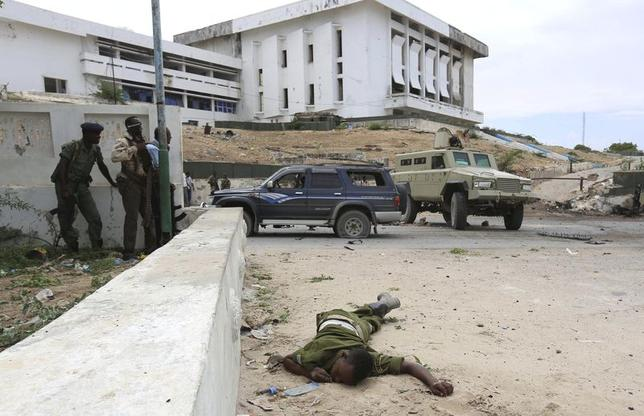 Somali government soldiers take positions near the body of their colleague who was slain during a clash with Al Shabaab militants outside the Parliament in the capital Mogadishu, May 24, 2014. REUTERS/Feisal Omar