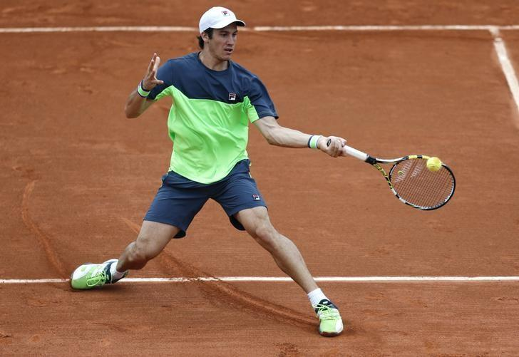Facundo Bagnis of Argentina hits a return to Julien Benneteau of France during their men's singles match at the French Open tennis tournament at the Roland Garros stadium in Paris May 26, 2014.           REUTERS/Jean-Paul Pelissier