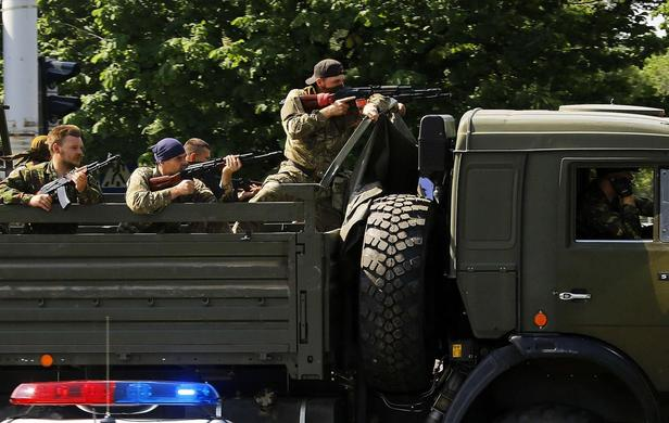 A military truck with armed pro-Russian militants drives through a police check-point towards the airport of the eastern Ukrainian city of Donetsk May 26, 2014. REUTERS-Yannis Behrakis