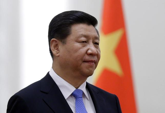 China's President Xi Jinping stands next to a Chinese national flag during a welcoming ceremony at the Great Hall of the People, in Beijing, in this November 13, 2013 file photo.   REUTERS/Jason Lee/Files