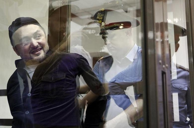 One of the defendants in the murder trial of Russian journalist and human rights activist Anna Politkovskaya, Rustam Makhmudov is escorted into a glass-walled cage before a court hearing in Moscow, June 3, 2013. Politkovskaya was assassinated in October 2006. REUTERS/Maxim Shemetov (RUSSIA  - Tags: CRIME LAW MEDIA) - RTX109Y2
