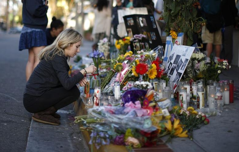 A woman lights a candle at a makeshift shrine for 20-year-old UCSB student Christopher Michael-Martinez outside a deli that was one of nine crime scenes after series of drive-by shootings that left 7 people dead in the Isla Vista neighborhood of Santa Barbara, California May 26, 2014.  REUTERS/Lucy Nicholson
