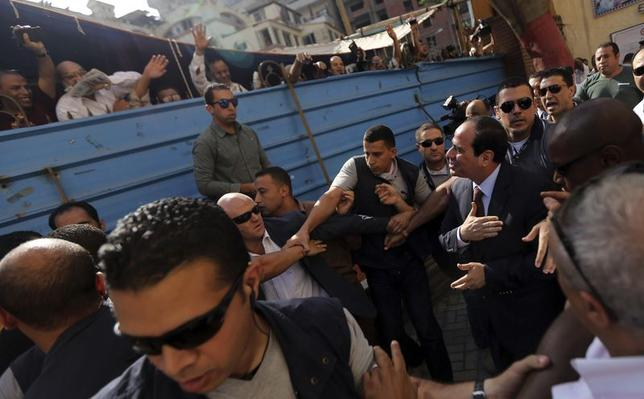 Presidential candidate and former army chief Abdel Fattah al-Sisi gestures to his supporters as he arrives with his bodyguards at a polling station to cast his vote during the presidential election in Cairo, Egypt, May 26, 2014. REUTERS/Amr Abdallah Dalsh