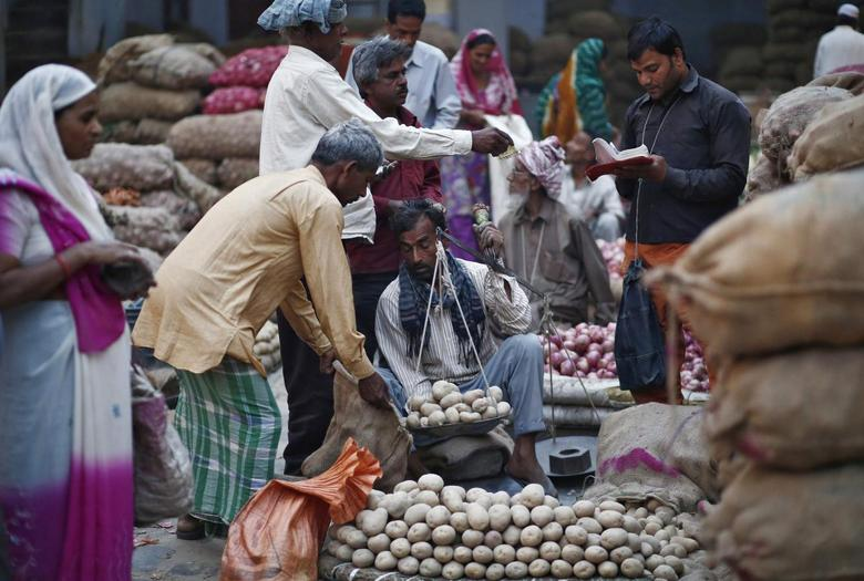 A vendor weighs potatoes for a customer at a vegetable wholesale market along a roadside in the old quarters of Delhi April 15, 2014. REUTERS/Anindito Mukherjee/Files