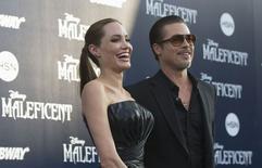 """Angelina Jolie et Brad Pitt lors de la première de """"Maléfique"""" à Los Angeles. L'acteur américain a été victime du trublion des tapis rouges, un journaliste de la télévision ukrainienne, Vitalii Sediuk, qui a sauté par dessus une barrière et l'a frappé au visage, sans gravité. /Photo prise le 28 mai 2014/REUTERS/Mario Anzuoni"""