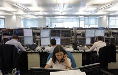 Трейдеры в торговом зале инвестбанка Ренессанс Капитал в Москве 9 августа 2011 года. Российский фондовый рынок демонстрирует в четверг настрой на продолжение роста этого месяца, и снизившиеся сразу после публикации отчетов акции Сбербанка и Мегафона быстро вернулись в общий строй. REUTERS/Denis Sinyakov