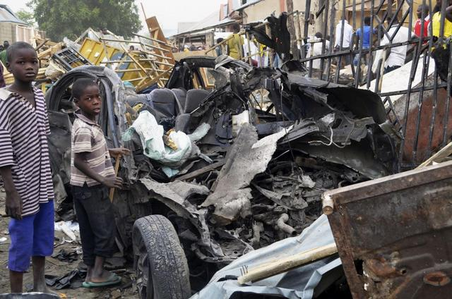 Two boys stand near the charred chassis of a vehicle after a bomb attack believed to have been carried out by the Islamist militant group Boko Haram that killed at least 10 people near a busy market area, in Ajilari-Gomari in Maiduguri in this March 2, 2014 file photo. REUTERS/Stringer/Files