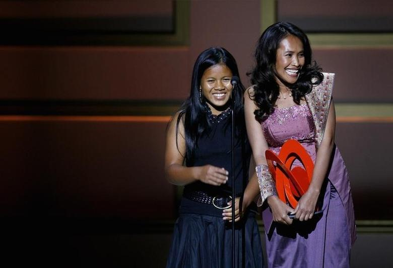 Cambodian activist Somaly Mam (R) accepts a ''Woman of the Year'' award with a child she rescued from sexual slavery, during the 2006 Glamour Magazine ''Women of the Year'' Honors award show in New York City October 30, 2006. REUTERS/Lucas Jackson
