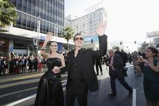 "Cast member Angelina Jolie and actor Brad Pitt wave at fans as they arrive at the premiere of ""Maleficent"" at El Capitan theatre in Hollywood, California May 28, 2014.  REUTERS/Mario Anzuoni"