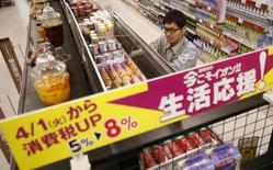 Un empleado de un supermercado cambia los precios de los productos bajo un aviso que informa de un alza al impuesto a las ventas, antes de la apertura del local en Chiba, al este de Tokio, 31 de marzo, 2014. El índice de precios subyacentes al consumidor escaló un 3,2 por ciento en abril frente al mismo mes del año pasado, mostraron el viernes datos del Gobierno, la mayor ganancia desde febrero de 1991, ya que un alza del impuesto a las ventas impulsó los precios a nivel general. REUTERS/Yuya Shino